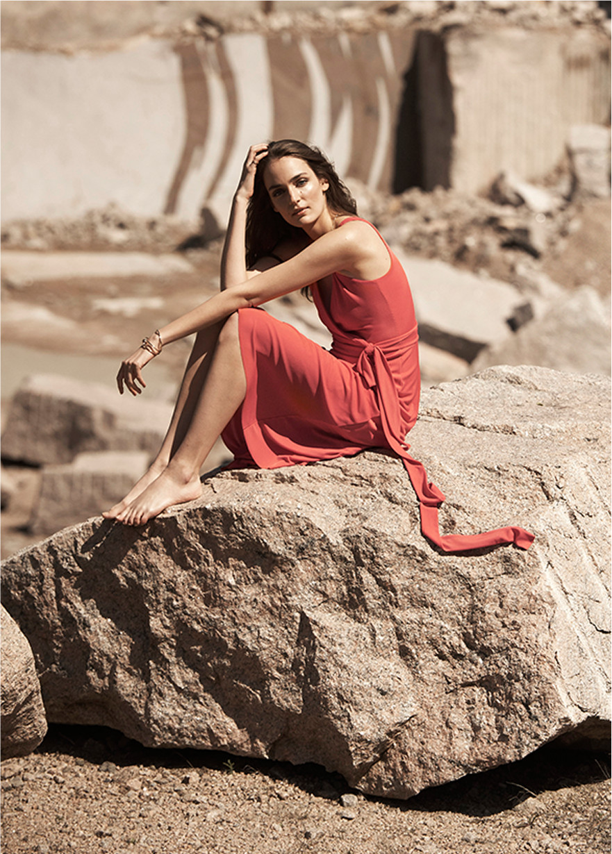 A woman sits on a rock in the sun wearing a colorful red sundress.