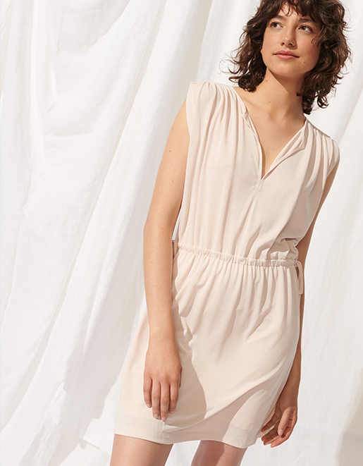 Woman in summer essentials—pleated jumpsuit, silky camisole, easy essentials.