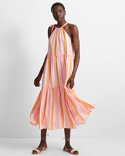 A woman stands, ready to twirl, in a pink striped sundress.
