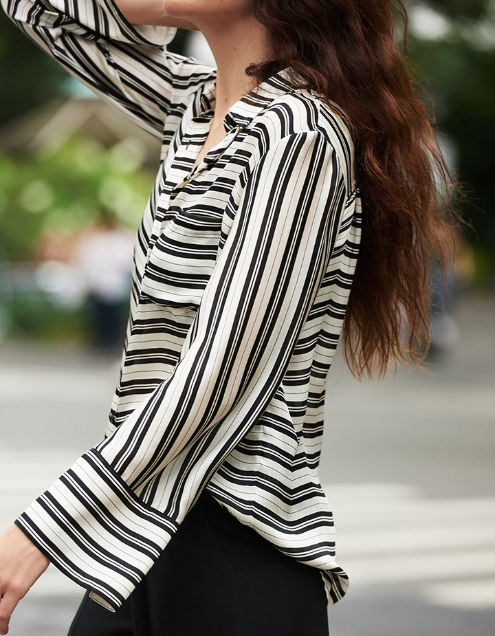 Woman in silk stripe blouse and other modern essentials.