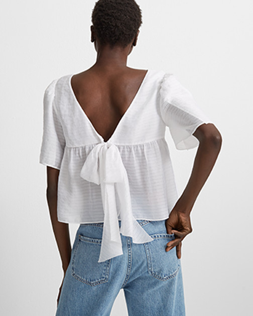 A woman, shown from behind, wears a breezy summer blouse with an open back.