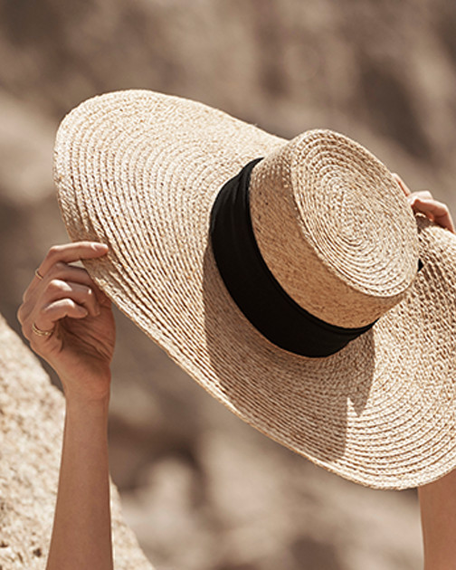 A woman holds up a straw hat in the sun.